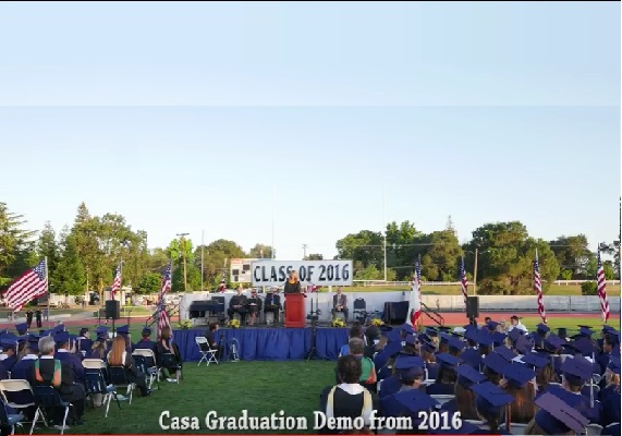 Click the title to view.<br>Live event, a graduation, filmed outdoors compensation for wind noise and captured sound from the microphone feed filmed with multiple cameras.